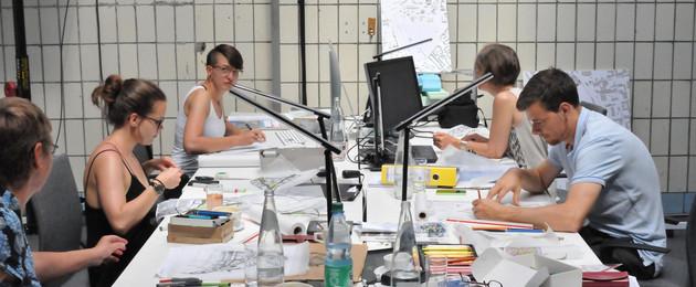 Blick auf einen Tisch, an dem von beiden Seiten Planer/-innen sitzen.