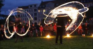Abendstimmung mit Feuerkünstlern beim Tanzfest 2010 auf einer Wiese