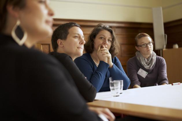 Ausschnitt eines Arbeitskreises. Einige Frauen sitzen um einen Tisch. Drei blicken in eine Richtung, eine vierte Frau sieht direkt in die Kamera.
