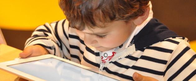 Kleiner Junge, der auf ein Tablet schaut