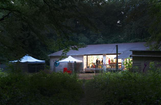 Ein flaches Gebäude umgeben von Bäumen. Im inneren brennt Licht, man sieht Menschen darin. Vor dem Haus stehen zwei Pavillons.