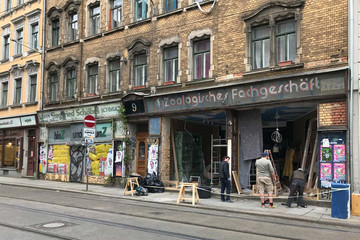 Bild wird vergrößert: In ein Ladengeschäft eines unsanierten Gebäudes wird ein Ladenfenster gebaut. Man sieht die Handwerker bei der Arbeit.