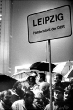 """Bild wird vergrößert: Schwarz-Weiß Foto einer Demonstration im Herbst 89 mit einem Schild """"Leipzig - Heldenstadt der DDR"""""""
