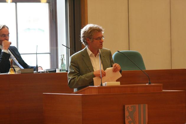 Ein Mann in Hemd und Jacket steht am Rednerpult und spricht. Him Hintergrund zu erkennen: Oberbürgermeister Burkhard Jung.