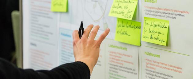 Blick auf eine Pinnwand, eine Hand mit Stift klebt gerade einen Zettel an.