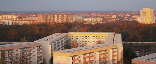 Im Abendsonnenschein sieht man über Dächer von Plattenbauten hinweg viel Grün.