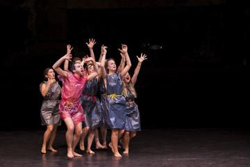 Bild wird vergrößert: Mehrere Theaterschauspieler auf der Bühne in Müllsäcke gekleidet mit Seilen als Gürtel. Sie heben die Hände in die Luft und schreien.
