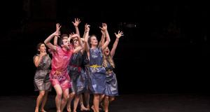 Mehrere Theaterschauspieler auf der Bühne in Müllsäcke gekleidet mit Seilen als Gürtel. Sie heben die Hände in die Luft und schreien.