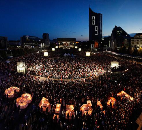 """Blick über den Augustusplatz mit tausenden Besuchern und dem erleuchteten Schriftzug """"Leipzig 89""""."""
