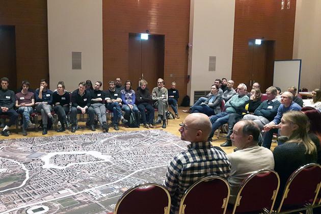 Menschengruppen sitzt auf Stühlen rund um einen Kartenteppich