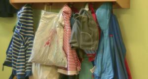 Schulsachen und Kinderkleidungen hängen an mehreren Kleiderhaken