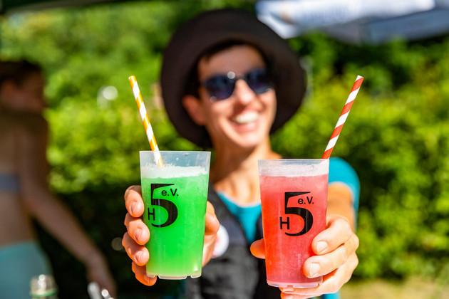 Eine Frau mit Hut hält zwei Gläser mit einem rotem und einem grünem Cocktail in die Kamera.