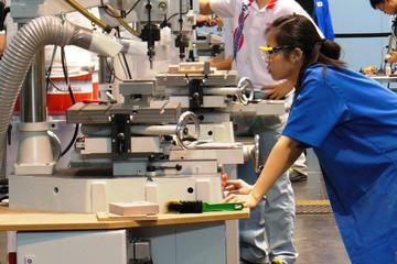 Bild wird vergrößert: Junge Frau bei den WorldSkills 2013 in Leipzig mit Arbeitsschutzbrille und im blauen Kittel vor großer Technik.