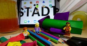 Stifte, Legofiguren, Tablet, Flasche und Luftballons liegen auf einem Tisch.