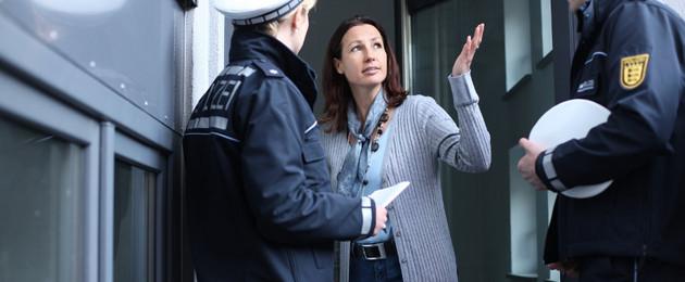 Zwei Polizisten befragen eine Zeugin an der Wohnungstür.