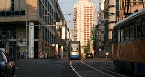 Straßenbahnen und Autos auf der Straße, im Hintergrund das Wintergartenhochhaus