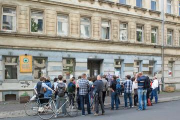 Bild wird vergrößert: Eine Gruppe Menschen steht vor einem Gebäude und hört einem Vortragenden zu