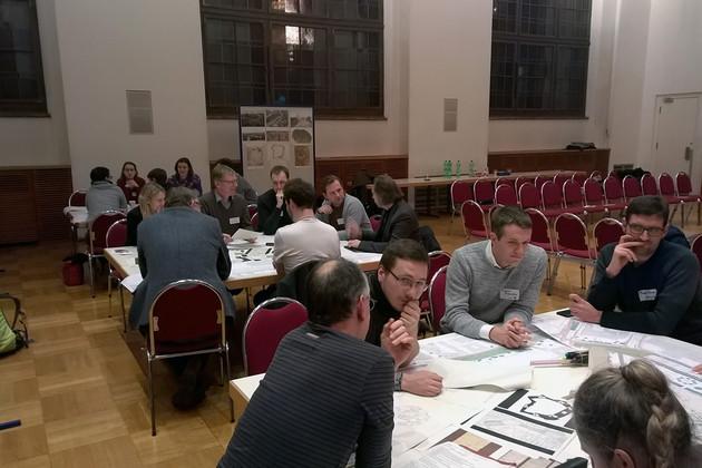 Menschen sitzen in mehreren Gruppen an verschiedenen Tischen und diskutieren. Auf den Tischen liegen viele Pläne und Skizzen.