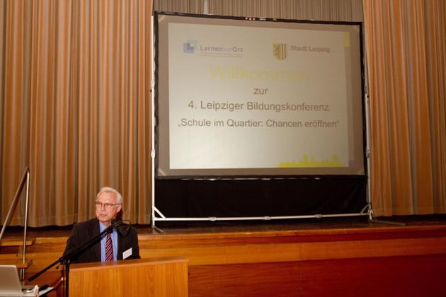 Ein ergrauter Mann mit Brille hinter einem Stehpult stehend. Er spricht, während im Hintergrund auf einer Projektionsfläche erläuternde Texte abgebildet werden.