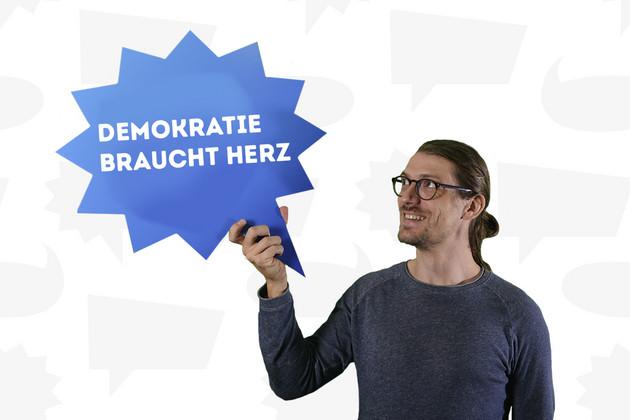 """Ein Mann hält eine Sprechblase mit dem Statement """"Demokratie braucht Herz""""."""