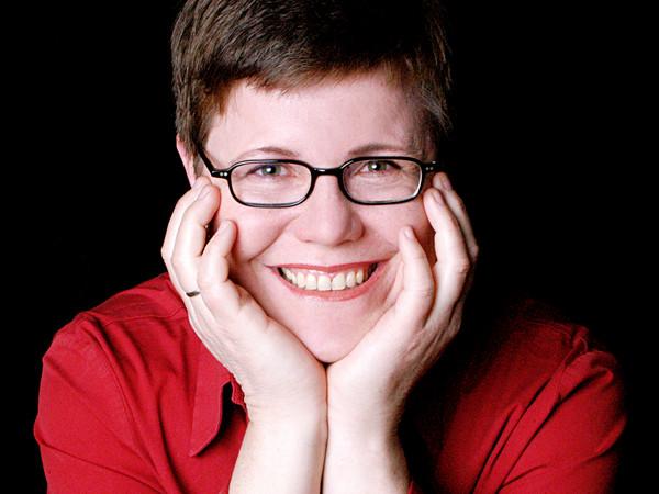 Eine Frau mit kurzen braunen Haaren und rotem Pullover und Brille lächelt ins Bild.