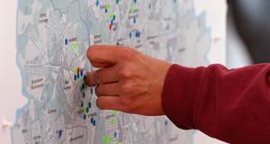 Eine Hand klebt Punkte auf eine Stadtkarte.