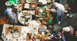 Besucher und Händler an einem Flohmarkttisch von oben fotografiert.