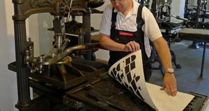 Druck an einer Kniehebelpresse im Museum für Druckkunst Leipzig