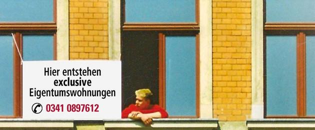 """Altbaufassade mit Person, die aus dem Fenster schaut. Daneben ein Schild """"Hier entstehen Eigentumswohnungen"""""""