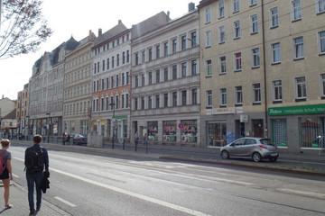 Bild wird vergrößert: Die Georg-Schumann-Straße mit mehrstöckiger Häuserbebauung, Verkehrsanlagen der Straßenbahn, einige Passanten und Autos.