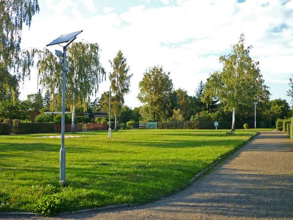 Grünfläche und Weg. Am Wegesrand steht ein Pfosten mit einem Bewegungsmelder.