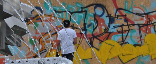 Junger Mann besprüht eine Graffiti-Wand