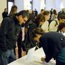 Zahlreiche Menschen drängen sich um Tische voll Listen, in denen sie sich in die Veranstaltungen einschreiben können.
