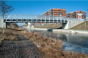 Bild wird vergrößert: Über ein Gewässer führt eine neue Stahlbrücke. Im Hintergrund sind mehrstöckige Wohnhäuser im Rohbau zu sehen.