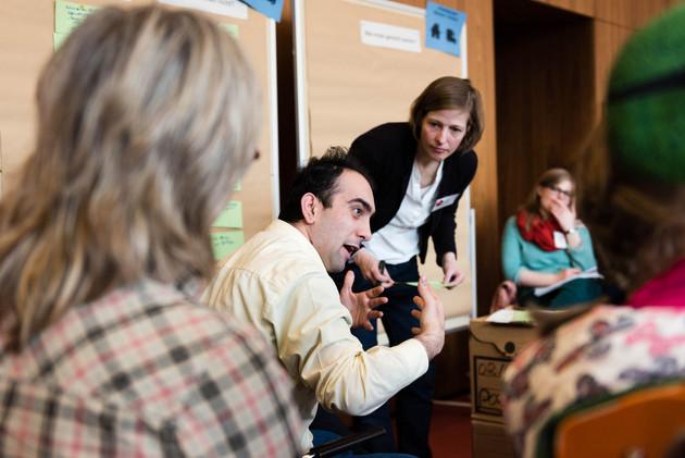 Teilnehmerinnen und Teilnehmer diskutieren in einer Kleingruppe. Ein Mann erklärt etwas und gestikuliert dabei. Die Moderatorin steht neben ihm und folgt aufmerksam seinen Ausführungen.
