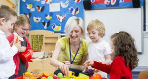 Eine Erzieherin spielt mit Kindern an einem kleinen Tisch