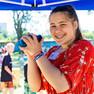 Eine Jugendliche mit rotem Kleid und Shaker in den Händen lacht in die Kamera.