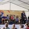 Der Bürgermeister Martin Fabian eröffnet auf der Bühne den 18. Tag der Begegnung. Vor der Bühne sitzt das Publikum. Im Hintergrund sitzt eine Trommlergruppe.