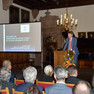In einem historischen Saal mit großen Gemälden an den Wänden steht ein Mann an einem Rednerpult und spricht zum Publikum.