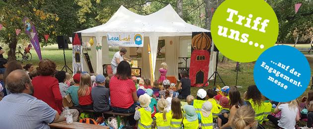 Im Park ist ein Zelt aufgebaut, in dem eine Märchenerzählerin vor einer großen Gruppe von Kindern liest.