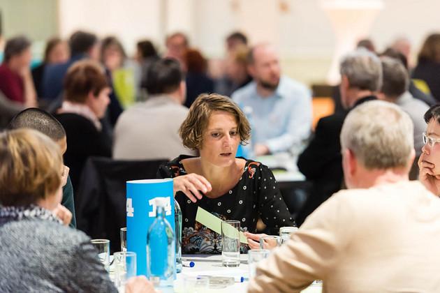 Diskussion am Tisch, eine junge Frau spricht.