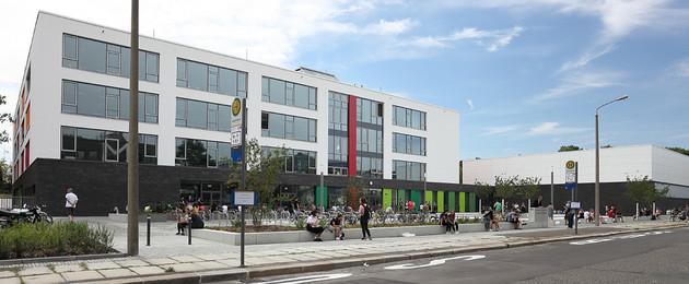 modernes Schulgebäude mit vorgelagerten Radabstellflächen und Hochbeeten