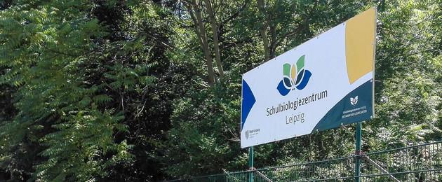"""großes Schild mit dem Logo des Schulbiologiezentrums und dem Schriftzug """"Schulbiologiezentrum Leipzig"""" vor Bäumen"""