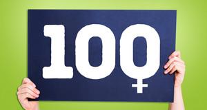 Zwei Hände halten ein blaues Schild nach oben. Darauf ist die Zahl 100 zu sehen, wobei eine 0 an das Venussymbol erinnert.