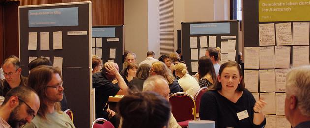 Viele Menschen sitzen an Tischen in einem Raum und diskutieren miteinander. Daneben stehen Tafeln, an denen Ergebnisse auf Zetteln festgehalten werden.