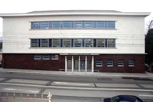 Gebäude der Bibliothek Plagwitz von außen über die Straße gesehen, Erdgeschoss mit roten Klinkern, oben heller Strukturputz.