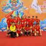 Mannschaftsfoto der Leipziger Drachenbootfahrer in roten Mannschaftsoutfit auf dem roten Teppich, im Hintergrund ein orange-blaues Werbeplakat für das Drachenbootfestival