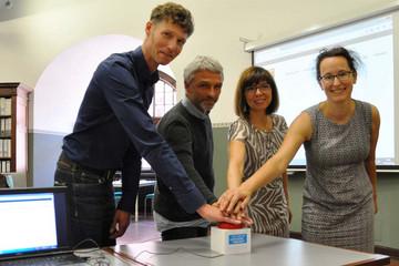Bild wird vergrößert: Der Startknopf für die neue Website wird gedrückt, man sieht zwei Männer und zwei Frauen