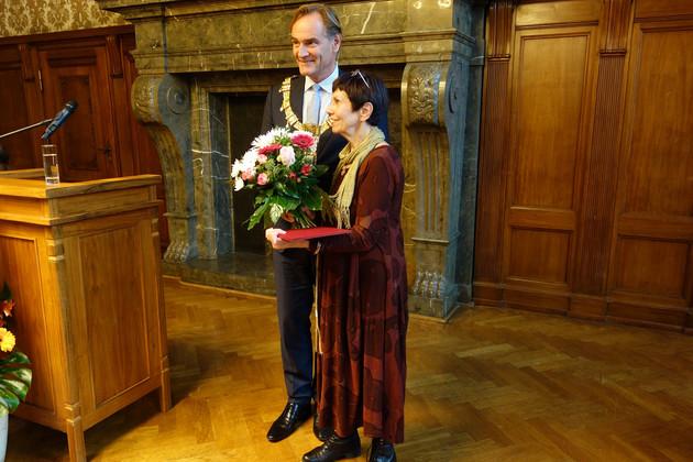 Oberbürgermeister Burkhard Jung und die Preisträgerin des Louise-Otto-Peters-Preises 2016 stehen beisammen. Herr Jung überreicht einen Strauß Blumen.