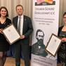 Herr Bonew und Frau Renner sowie Frau Langer halten zwei gerahmte Urkunden mit der Auszeichnung für die aktivste deutsch-amerikanische Städtepartnerschaft in 2018, daneben ein weißes Roll Up der Steuben-Schurz Gesellschaft